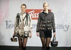 Models tragen Kleider aus Kochtöpfen und Pfannen